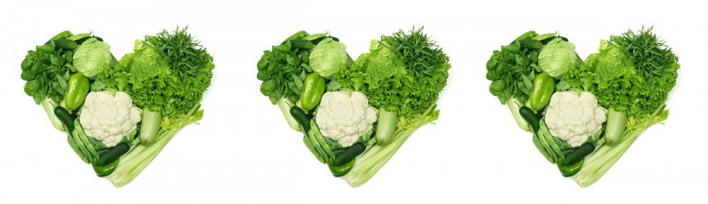 Pile of vegetables shaped as heart isolated on white background